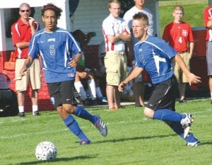 Sophomore Anas Morsi (5) and senior Brandon Brown (18) work the ball up the field for the Cavaliers' boys' soccer team during a September game.