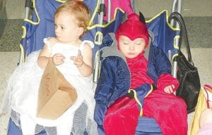 Little Angel Ana Harris, 15 months, gathers candy while her twin LIttle Devil Anthony sleeps at the Trick or Treats So Kids Can Eat fundraiser sponsored by the CAHS Drama Club. See page 11 for more.
