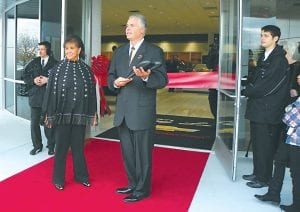 Patsy Lou Williamson, owner, and Larry White, general get ready to cut the ribbon for the reopening of the newly renovated Chevrolet dealership.