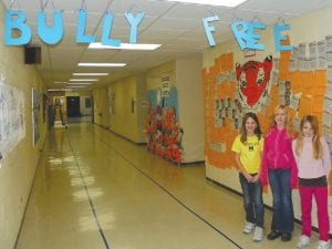 Newly trained anti-bullying peer mediators Cassidy Idalski, Kyah Grimsley and Alicia Todd stand under an anti-bulling pledge board.