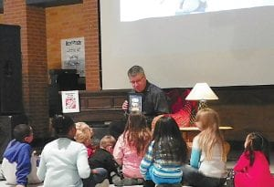 "Photo by Rhonda S. Sanders Carman-Ainsworth Superintendent Bill Haley reads ""Twas the Night Before Christmas"" using an iPad."