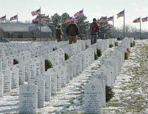 Visitors to the Great Lakes National Cemetery pay their respects to fallen comrades during the ceremony.