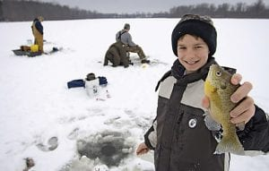 Snow cover warms an ice-covered lake putting anglers on caution.