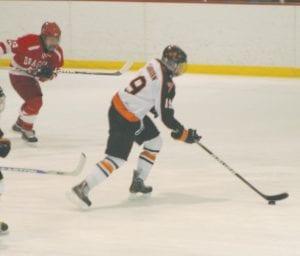 Junior Forward Drew Sanborn skates through the Swartz Creek defense.