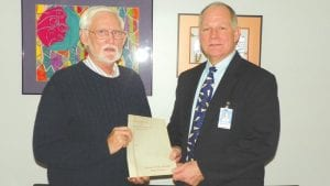 Don Nichols of Flint presents 1949 dedication booklet for the old Mandeville High School to Dave Swierpel, Carman Ainsworth Schools Director of Professional Learning & Community Services.