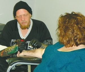 Drew Blaisdell, tattoo artist and church member, works on a tattoo for Cortney Spalding at Serenity Tattoo inside The Bridge Church on Corunna Road.