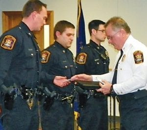 Flint Township Police Chief George Sippert awards Medal of Distinquished Services to (l to r) officers Matthew VanLente, Jerome Grzanka and Doug Hart.
