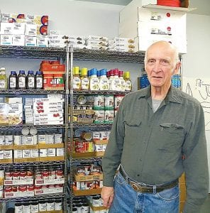 Bob Moore shows shelves filled only three days before with food items for needy seniors.