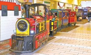 All aboard! Adi Twina, owner and operator of a new trackless train ride at Genesee Valley Center, ferries passengers on a ride throughout the mall.