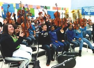 Members of the Carman-Ainsworth Middle School band hold up new instruments provided to them through a matching grant from the Classic for Kids Foundation.