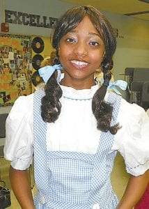 "Tahirah Gaines, above, played the role of Dorothy among cast members for ""The Wizard of Oz'' who gathered backstage last week for pre-performance drills including song run-throughs, vocal and physical warm-up exercises, a pep talk and high fives. Five shows at Carman-Ainsworth High School took place on Wednesday though Sunday included parts played by children of faculty and from various C-A elementary schools, said Delynne Miller, theater director."