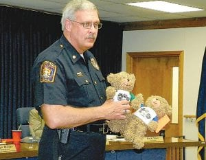 Lt. Tim Jones of the Flint Township Police Department holds teddy bears that police will use to calm frightened children at emergency events.