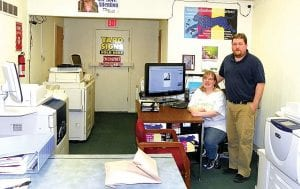 Zuddles the cheetah overlooks the workspace of Kelly and Carl Sharkey at their copy, design and printing shop.