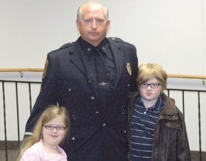 Sgt. Randy Kimes of the Flint Township Police Department with his grandchildren following his proKIMES motion, April 16.