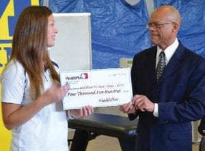 PT HEART Student Director of Funds Lauren Jarman accepts a check from HealthPlus Community Relations Administrator Louis Hawkins at the North End Soup Kitchen — the location of the student-run PT HEART clinic.