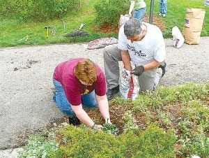 Tina Turner, of Faith Missionary Church gets help planting flowers from Gary Cox, a Gleaner member.