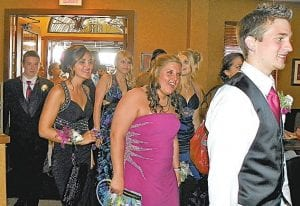"""A NIGHT TO REMEMBER — Thirty-two Carman-Ainsworth students and dates arrived on a party bus for dinner at Sorrento's in Flushing before traveling on to their senior prom at the Dow Event Center in Saginaw. This year's theme was """"Glow"""" for which many students carried glow-in-the-dark necklaces and bracelets to light up the prom atmosphere. This Carman- Ainsworth couple were among 32 prom goers who dined at Sorrento's in Flushing before traveling by party bus to their senior prom."""