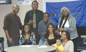 Lariah Simpson and Jalesia Johnson surrounded by family during Monday's signing.