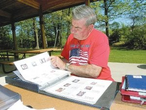 Donald McGowan of Clio looks through the scrapbook he has compiled of all fallen soliders from Michigan who will be recognized at a concert he is organizing next month.