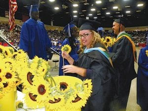 """CLASS OF 2012 — The Carman-Ainsworth Class of 2012 held commencement exercises May 31 at Perani Arena in Flint. Each of the 295 graduates were presented with the Class Flower. Students also heard a performance by Robby Williams of the Class song """"Good Life"""" by OneRepublic."""