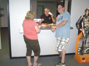 Owner Chuck Nelson assists customers Donn and Cindy Peel as the couple purchases a new cellular phone.