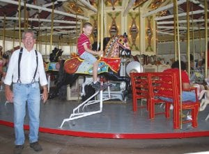 Cliff Black stands near Crossroads Village and Huckleberry Railroad's Charles W. Parker Carousel which turns 100 this year.