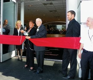 Patsy Lou Williamson and husband Don cut the ribbon at a Grand Re-opening celebration last week of her Buick/GMC dealership on Corunna Road.