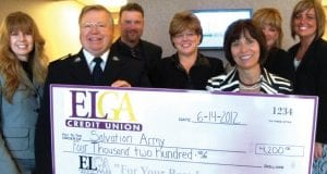 Karen Church, CEO of ELGA Credit union surrounded by ELGA Credit Union employees presents a check for $4,200 to William Goodwill, Genesee County Business Manager of The Salvation Army to help area families with food and shelter.