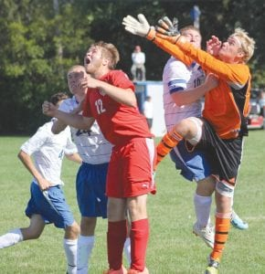 Carman-Ainsworth goalie Andrew Ramirez (in orange) leaps for a corner kick amidst a crowd of players in Monday's game against Creek at Carman-Ainsworth.