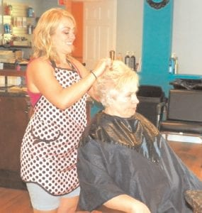 Shanon Wooley styles the hair of a customer in her new shop.