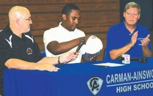 Carman-Ainsworth basketball star Denzel Watts places the Alabama-Birmingham cap on his head last Thursday flanked by Bill Schnorenberg (left) and hoops coach and AD, Bob Root.