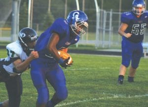 Carman-Ainsworth's Lorenzo Redmond drags a defender as he tries for more yardage.
