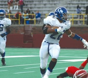 Gerald Holmes gallops for some of his 122 yards on the fast turf at Atwood Stadium last Friday.