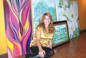 Sherri Ananich with some of her paintings on display at the Yoga Path, 1086 N. Irish Rd., in Davison Township.