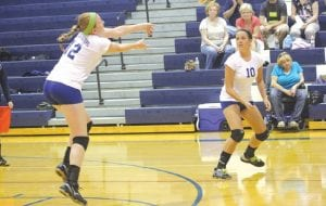 Junior Jessica McClung (#12) and sophomre Jessica Smith (#10) look to keep the ball in play for the Carman-Ainsworth varsity volleyball team.