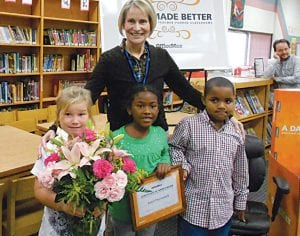 Janet Duvendeck with Randels students holding flowers and framed certificate of appreciation presented at day in her honor.
