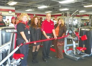 George Zerka prepares to cut the ribbon on his new Snap Fitness franchise with Tracey Tucker, Flint Township economic enhancement director, family members and staff.