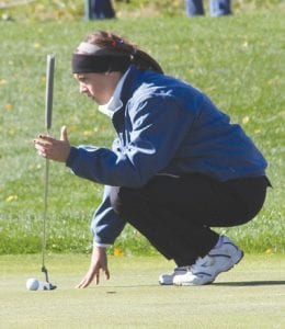 Carman-Ainsworth's Mikaila Garrison assesses her putt options at the very windy Twin Lakes Golf and Swim Club last Thursday.