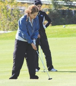 Carman-Ainsworth's Albany McComb watches her putt roll at the Division 1 regional at Twin Lakes Golf and Swim Club in Oakland Township last Thursday. Teams faced cold temperatures and a relentless 20-mph wind the whole day.