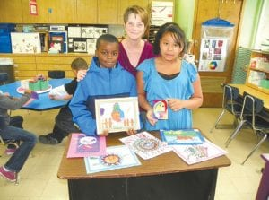 Dye Elementary art teacher Tina McGinnis with fifth-graders Montrel and Allana whose art she chose to turn into a magnet.