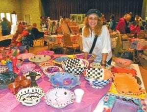 SHOPPING SPREE — A variety of vendors selling unique wares offered a chance to start Christmas gift shopping at the Holiday Bazaar on Sunday sponsored by the Sisterhood of Congregation Beth Israel at Dye and Calkins Road. Marla Whitesman shows off colorful pottery she created many years ago.