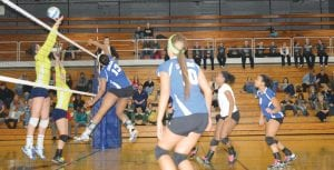 Carman-Ainsworth's Breanna Hudson (13) pounds a kill.