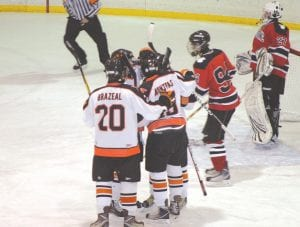 At right: Nick Brazeal (graduated), Mickey Montpas, back this season as a senior, celebrate with teammates after a goal is scored against Grand Blanc at a home game at Flint Iceland Arenas.