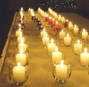 Candles lit in memory of loved ones glow at the recent annual vigil held by local volunteers of the Genesee County Mothers Against Drunk Driving chapter.