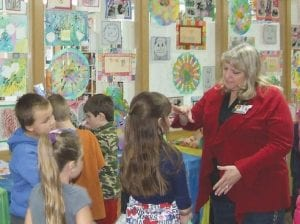 Debra Hancock, Grand Blanc Board of Education Vice President, speaks with students at Brendel Elementary during a recent art exhibit.