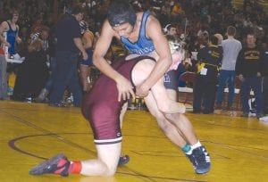 Carman-Ainsworth's Shaquel Paulicek tries to escape the takedown of Davison's Matthew Miller at the Genesee County varsity wrestling meet hosted by the Cardinals.