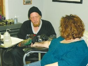Tattoo artist Drew Blaisdell practices his trade at the Bridge Church in Flint Township.