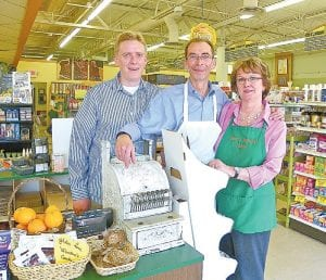 In a photo taken in February 2012, Don and Jean Wolfe and their son Drew stand behind a just-for-show antique cash register probably used by the first generation owners of Dale's health food store.