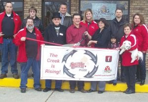 RIBBON CUTTING — In The Dog House Bakery, 9061 Miller Rd., in Swartz Creek, recently held a ribbon cuting event for their shop with the support of the Swartz Creek Chamber of Commerce. Here the owners of the store and members of the chamber pose for the event.