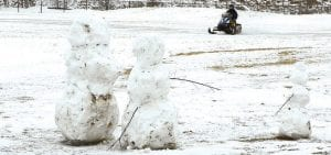 Some last minute snow fun as winter winds down. Snow family stands watch in large field, also popular with snowmobilers.